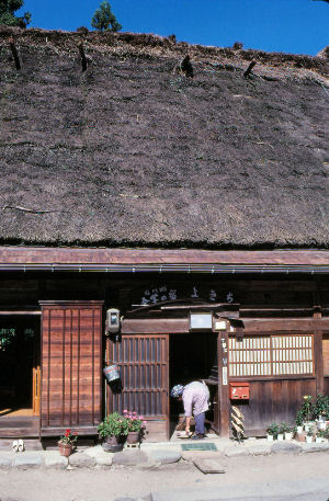 Shirakawa, Japan. An o-baachan cleaning her gassho house